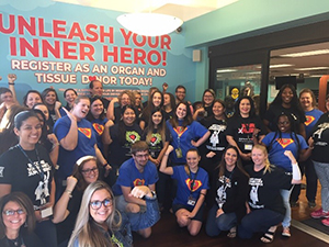 Tax Collector Ken Burton, Jr., and employees gathered in front of the Superheroes for Life mural
